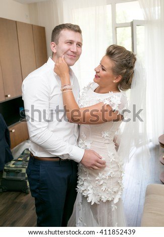 Portrait of happy bride rubbing grooms cheek at home - stock photo