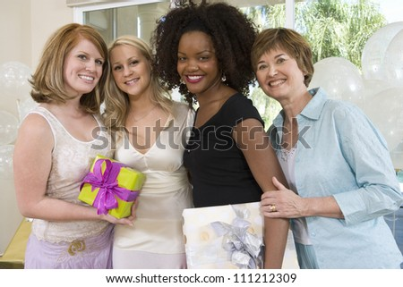 Portrait of happy bride with her friends and mother at party - stock photo