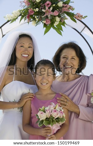 Portrait of happy bride with mother and flower girl standing against sky