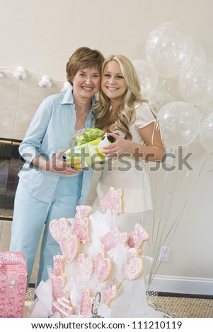 Portrait of happy bridge and her mother holding gift box at party - stock photo
