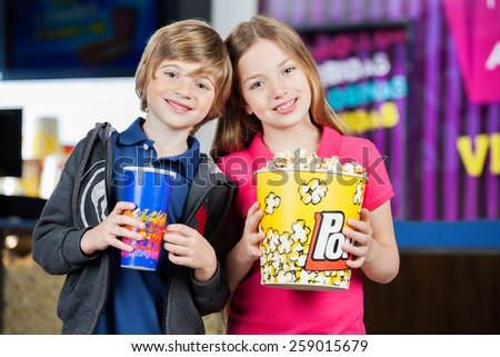 Portrait of happy brother and sister holding snacks against cinema concession stand - stock photo