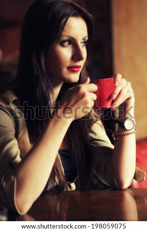 Portrait of happy brunette enjoying a cup of coffee - stock photo