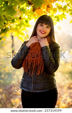 Portrait of happy brunette woman in scarf posing at autumn park - stock photo
