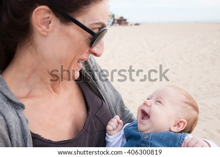 portrait of happy brunette woman mother grey shirt black sunglasses with two month age baby blue jeans dress embraced in her arms laughing in beach - stock photo