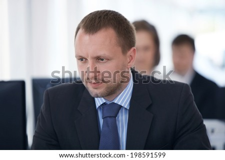 Portrait of happy business man with his colleagues in background  - stock photo