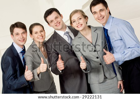 Portrait of happy business partners looking at camera with smiles and showing sign of okay