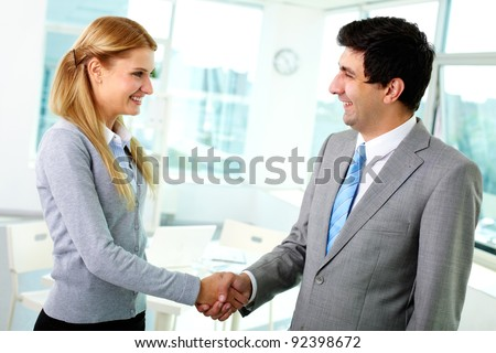 Portrait of happy business partners shaking hands at meeting - stock photo