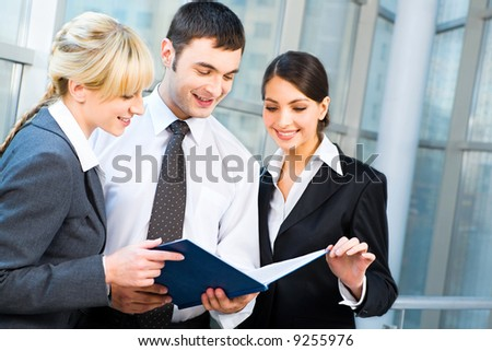Portrait of happy business people looking at working document