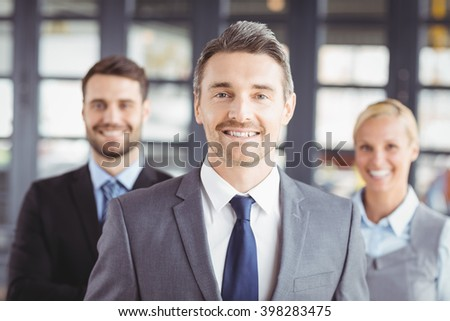 Portrait of happy business people wearing suit standing in office - stock photo