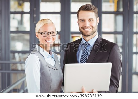 Portrait of happy business people with laptop standing in office - stock photo
