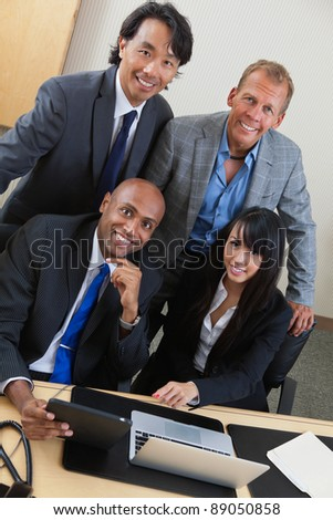Portrait of happy business people working on laptop together - stock photo