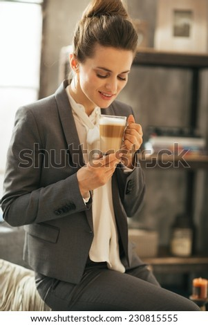 Portrait of happy business woman drinking coffee latte in loft apartment