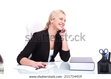 Portrait of happy business woman sitting on her desk. beautiful young blond laughing and talking on cell phone - stock photo