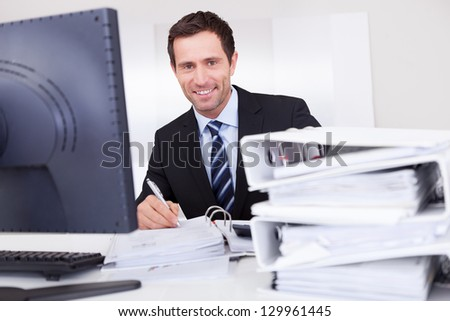 Portrait Of Happy Businessman At Workplace In the Office - stock photo