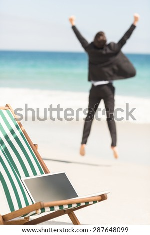Portrait of happy businessman cheering at the beach - stock photo