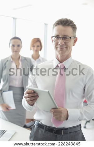 Portrait of happy businessman holding digital tablet with female colleagues in background at office - stock photo