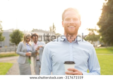 Portrait of happy businessman holding disposable cup with colleagues standing in background - stock photo
