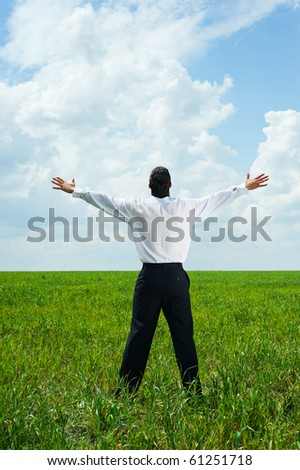 portrait of happy businessman in green field