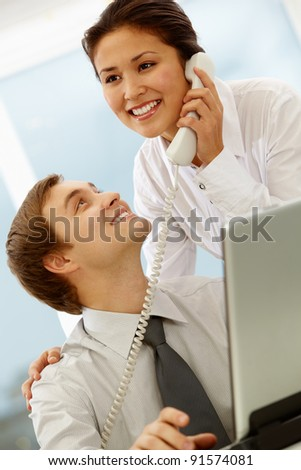 Portrait of happy businessman looking at his smiling secretary while she speaking on the phone
