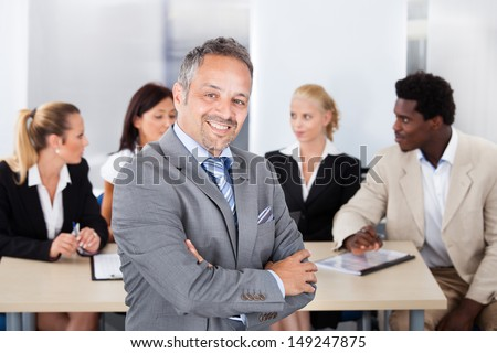 Portrait Of Happy Businessman Sitting In Front Of Colleagues - stock photo