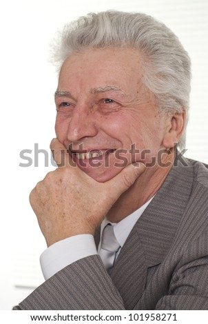 Portrait of happy businessman sitting on a light background