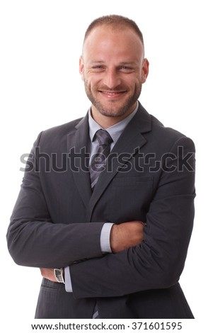 Portrait of happy businessman standing arms, smiling, looking at camera.