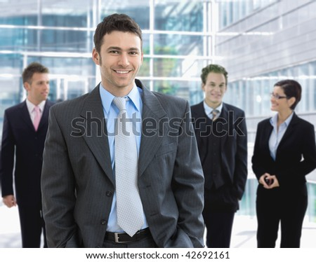 Portrait of happy businessman standing in office lounge smiling. - stock photo