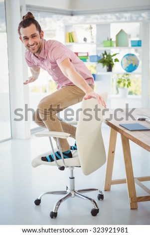 Portrait of happy businessman standing on chair in office - stock photo