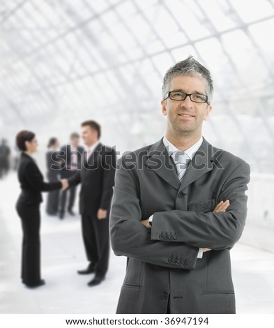 Portrait of happy businessman standing with hands crossed in office lobby, smiling.