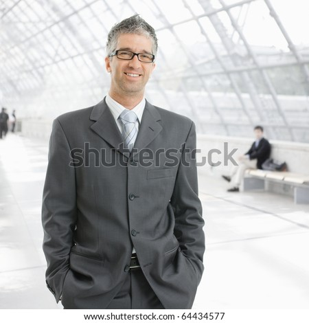 Portrait of happy businessman standing with hands in pocket in office lobby, smiling.? - stock photo