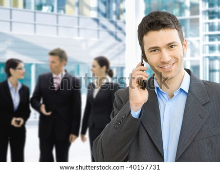Portrait of happy businessman talking on mobile in office lounge. - stock photo