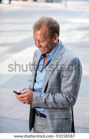 Portrait of happy businessman text messaging - stock photo