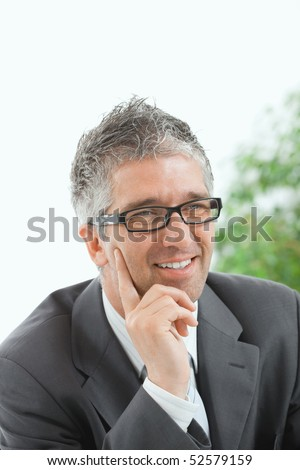 Portrait of happy businessman thinking, smiling.
