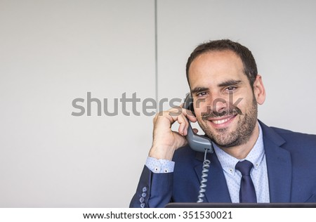 Portrait of happy businessman using landline phone at office desk - stock photo
