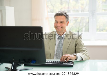 Portrait Of Happy Businessman Using Office Computer - stock photo