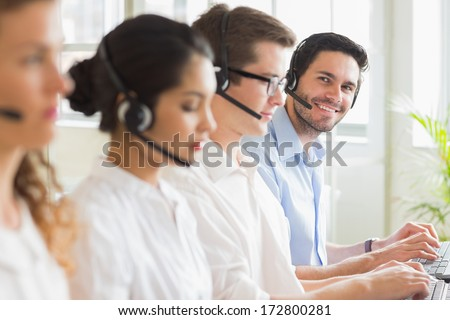 Portrait of happy businessman with colleagues working in call center - stock photo