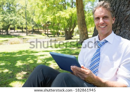 Portrait of happy businessman with digital tablet leaning on tree trunk in park