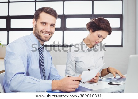 Portrait of happy businessman with document while female colleague sitting beside - stock photo