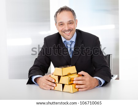 Portrait of happy businessman with golden bars at the office - stock photo