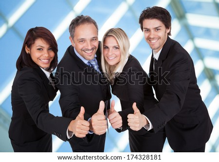 Portrait Of Happy Businesspeople Showing Thumb-up Sign
