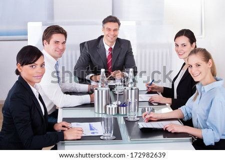 Portrait Of Happy Businesspeople Sitting At Desk Sharing Idea - stock photo