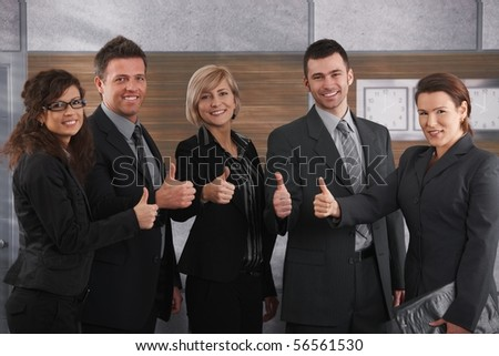 Portrait of happy businesspeople standing in office showing OK sign, smiling. - stock photo