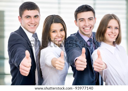 Portrait of happy businesspeople standing in office showing thumb up - stock photo