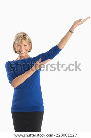 Portrait of happy businesswoman gesturing against white background - stock photo