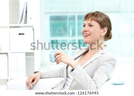 Portrait of happy businesswoman having coffee in office - stock photo