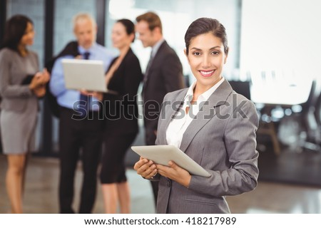 Portrait of happy businesswoman holding digital tablet in office and colleagues discussing in background - stock photo