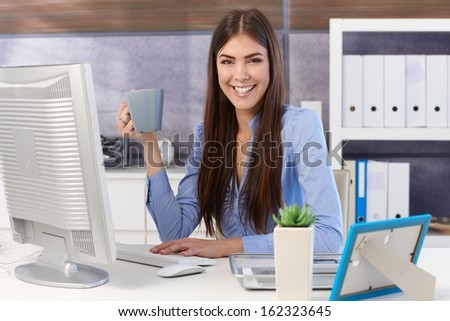 Portrait of happy businesswoman sitting at office desk with coffee mug handheld, smiling at camera. - stock photo