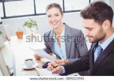 Portrait of happy businesswoman sitting beside male colleague at computer desk in office - stock photo
