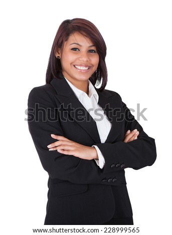 Portrait of happy businesswoman standing arms crossed over white background