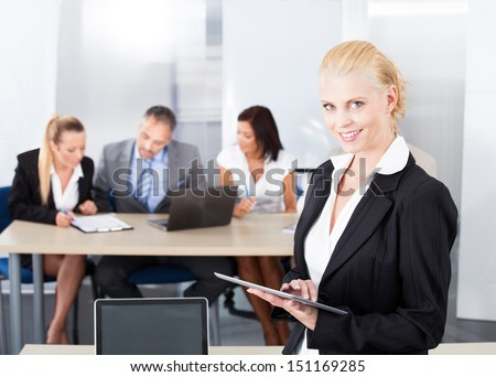 Portrait Of Happy Businesswoman Standing In Front Of Colleagues - stock photo